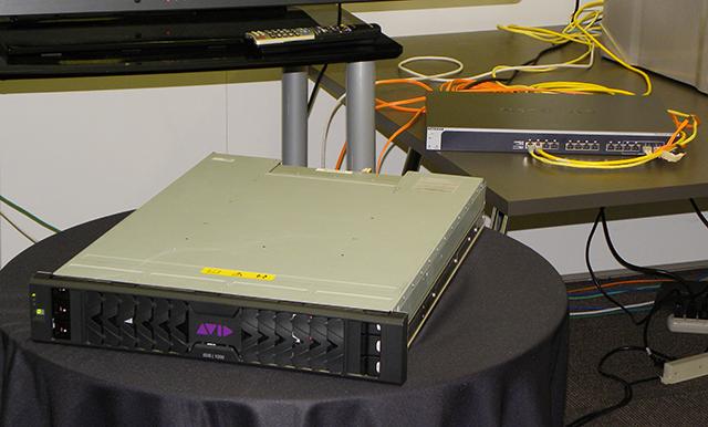 写真4 ISIS|1000とスイッチングハブ(右奥)。ISIS|1000とクライアントマシーンは高速スイッチングハブを介してのみ接続可能。同時接続クライアント数は最高24クライアントとなる。使用可能なスイッチングハブの指定があるので注意が必要だ(写真はNetgear製)。ISIS|1000のサイズはIECラック互換、奥行きが630mmもあるので、ビデオ業界標準のラックだと奥行きが多少厳しくなる
